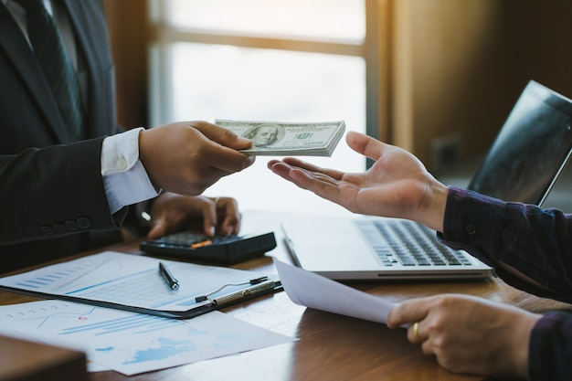 Homme d'affaires donnant de l'argent à son partenaire sur le bureau