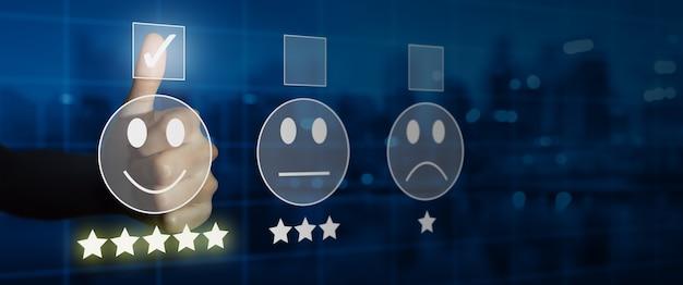 Homme d'affaires donnant une note avec une émoticône de visage souriant sur un écran tactile virtuel, une enquête de satisfaction client et un concept d'évaluation du service client.