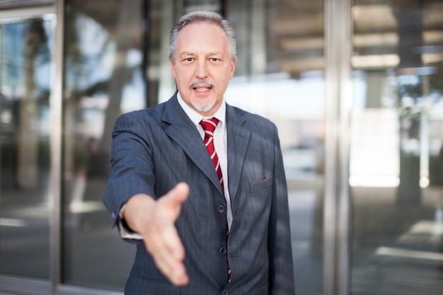 Homme d'affaires donnant une poignée de main devant son bureau