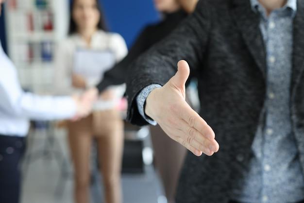 Homme d'affaires donnant sa main pour la poignée de main au partenaire sur fond de gros plan de collègues