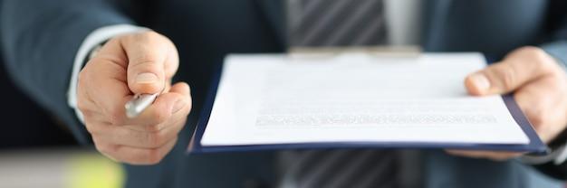 Homme d'affaires donnant un stylo à bille pour signer le concept de coopération commerciale en gros plan