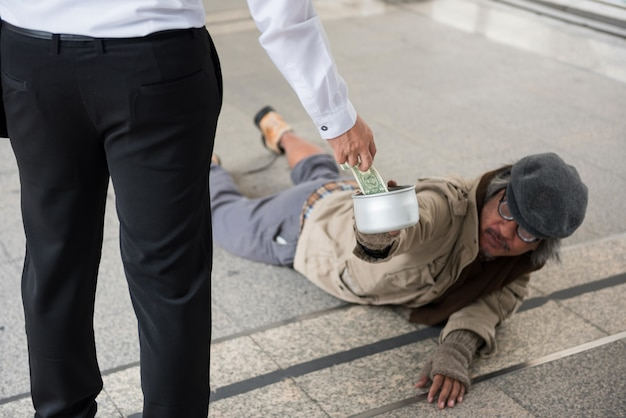 Homme d'affaires donne de l'argent à un homme sans abri handicapé