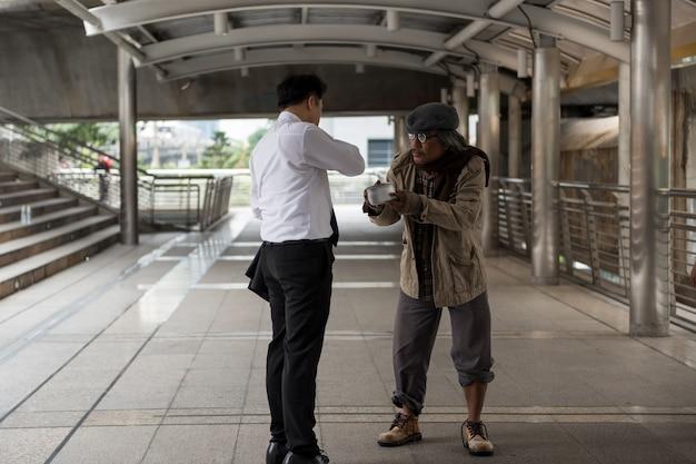 Homme d'affaires donne de l'argent à de vieux sans-abri