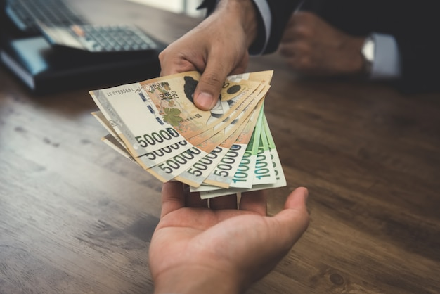 Homme affaires, donner, argent, coréen, gagné, billets banque, à, sien, partenaire