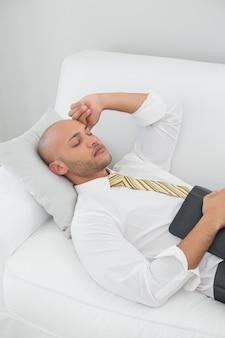 Homme d'affaires, dormir sur le canapé avec tablette numérique à la maison
