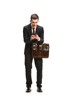 Homme d'affaires avec dossier bavardant sur le smartphone isolé sur mur blanc