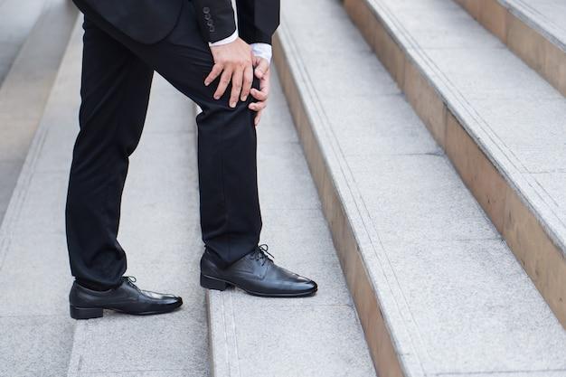 Homme d'affaires avec douleur au genou, concept d'obstacle