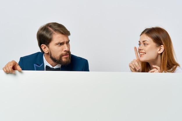 Homme d'affaires drôle et femme tenant une affiche promotionnelle