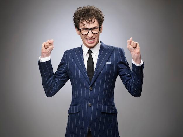 Homme d'affaires drôle de génie maléfique super excité. expression faciale d'acteur professionnel. souriant à pleines dents, serrant les poings.
