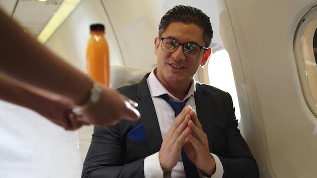 Homme d'affaires a du jus d'orange servi par une hôtesse de l'air en avion. concept de voyage d'affaires.