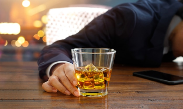 Homme d'affaires avec du whisky bourbon à la main, ivre dormant à la table du pub