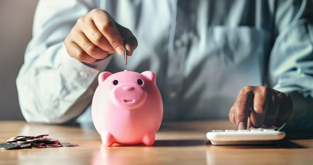 Homme d'affaires, économiser de l'argent concept. main, mettre pièces, dans, tirelire, et, utilisation, calculatrice