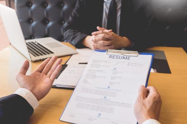 Homme d'affaires écouter un jeune homme attrayant expliquer ses réponses à l'entretien d'embauche de profil
