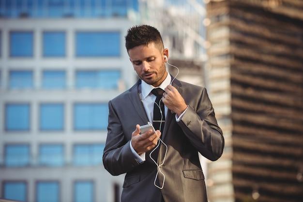 Homme affaires, écouter musique, sur, téléphone portable