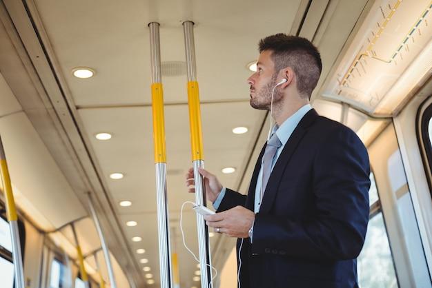 Homme affaires, écouter musique, et, utilisation, sur, téléphone portable