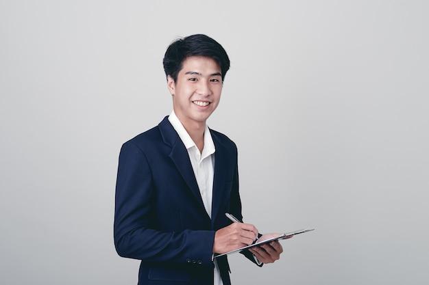 Homme d'affaires écrit dans un cahier sur blanc
