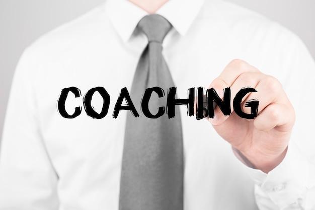 Homme d'affaires écrit mot coaching avec marqueur, concept d'entreprise