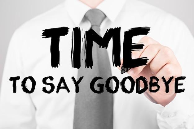Homme d'affaires écrit le mot temps de dire au revoir avec marqueur, concept d'entreprise
