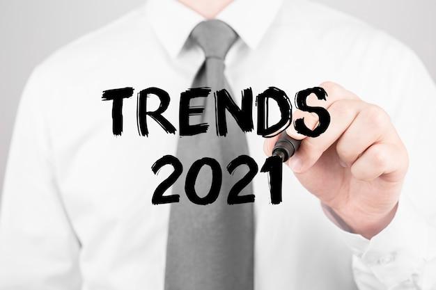 Homme d'affaires écrit le mot tendances 2021 avec marqueur, concept d'entreprise
