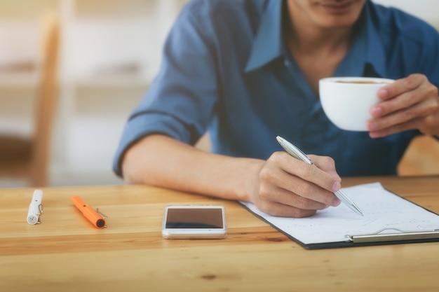 Homme d'affaires écrit la note et boire du café au bureau à domicile.