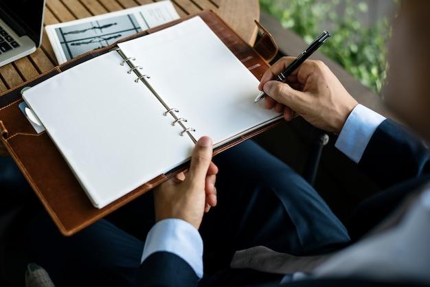Homme d'affaires écrit une note sur un cahier