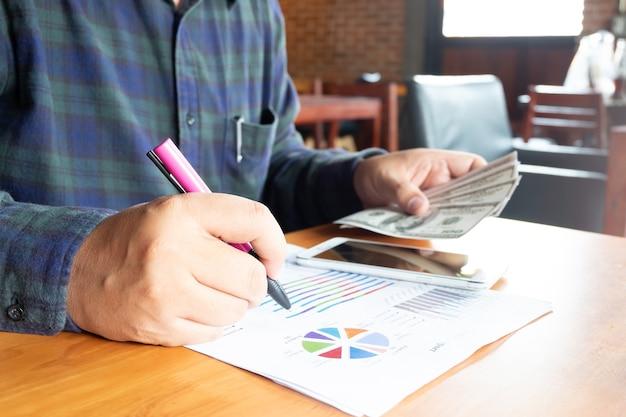 Homme d'affaires écrit sur papier détenant dollar billet de banque en main