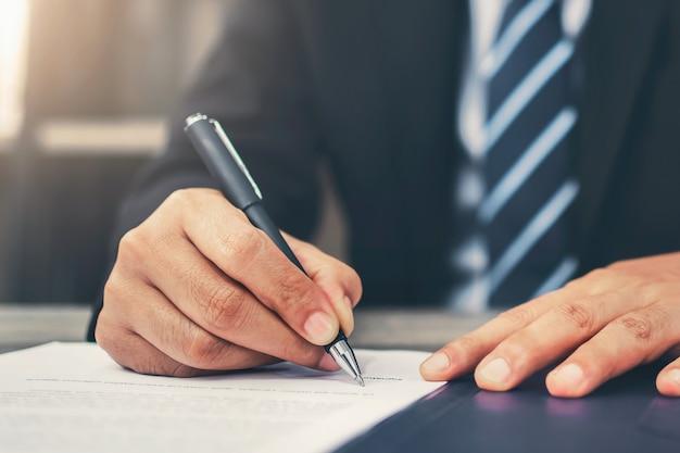 Homme d'affaires écrit la signature sur le document au bureau