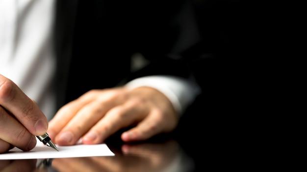 Homme d'affaires écrivant de la correspondance ou signant un document à l'aide d'un stylo-plume, gros plan sur une perspective à faible angle du papier et de ses mains avec copyspace