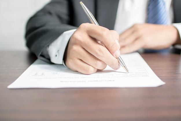 Homme d'affaires écrivant sur le formulaire de demande