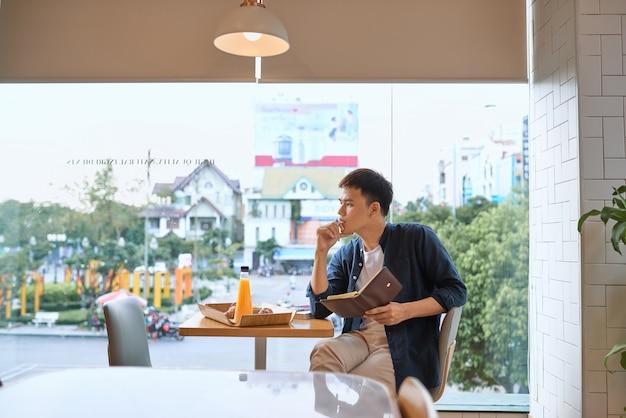 Homme d'affaires écrivant sur un ordinateur portable par la fenêtre du café, concentré sur le travail, vue latérale d'un jeune homme confiant travaille sur un ordinateur portable tout en s'asseyant et en écrivant dans un café, âgé de 20 à 30 ans.