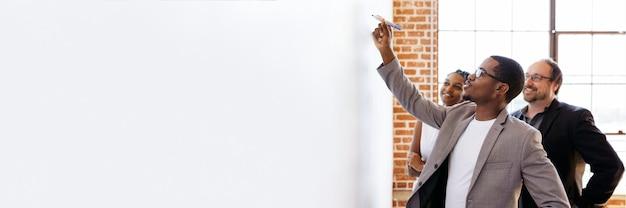Homme d'affaires écrivant sur un tableau blanc