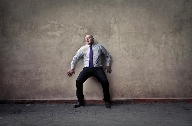 Homme d'affaires effrayé sur le mur