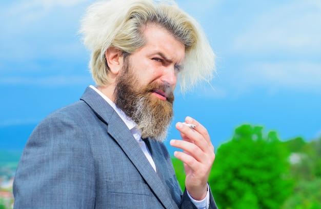 Homme d'affaires élégant avec cigarette, homme barbu fumant une cigarette, dépendance au tabac.