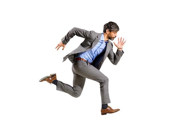 Homme d'affaires élégant en costume courant à grande vitesse dans une foulée aérienne isolée sur blanc conceptuel d'ambition, de délais, d'urgence et d'être en retard pour un ordre du jour