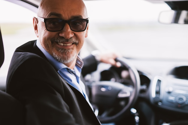 Homme d'affaires élégant professionnel gai mature dans un costume conduit une voiture en marche arrière.