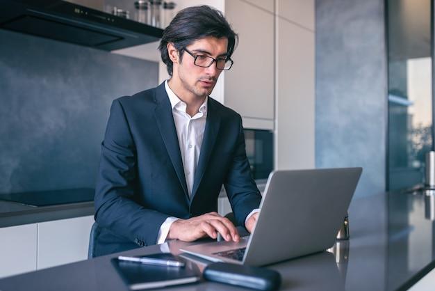 Homme d'affaires élégant travaille à domicile avec un ordinateur portable. concept de télétravail