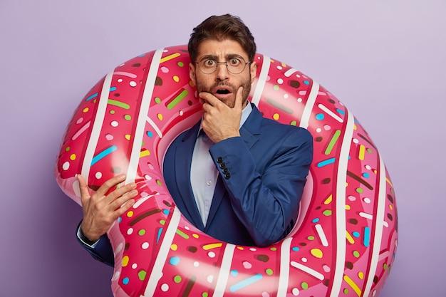 Homme d'affaires embarrassé posant en costume élégant au bureau