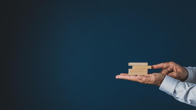 Homme d'affaires empilant des chevilles en bois dans la paume de sa main. sur fond bleu marine avec espace copie.