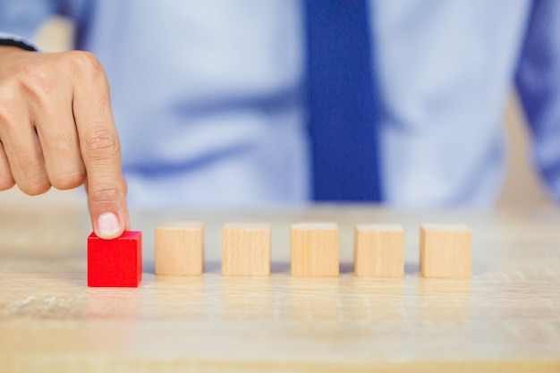 Homme d'affaires empiler des blocs de bois en étapes. concept de réussite de la croissance des entreprises