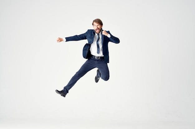 Homme d'affaires énergique dans un costume bleu saute sur un espace lumière succès joie émotions