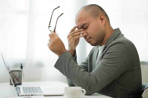 L'homme d'affaires enlève ses lunettes et se frotte les yeux, il ressent des maux de tête.