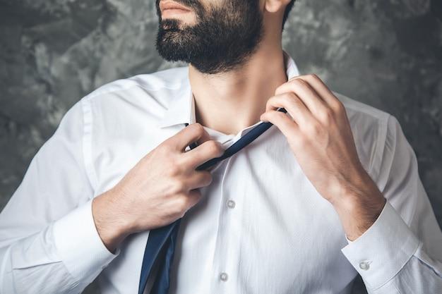 Homme d'affaires enlever la cravate sur fond sombre