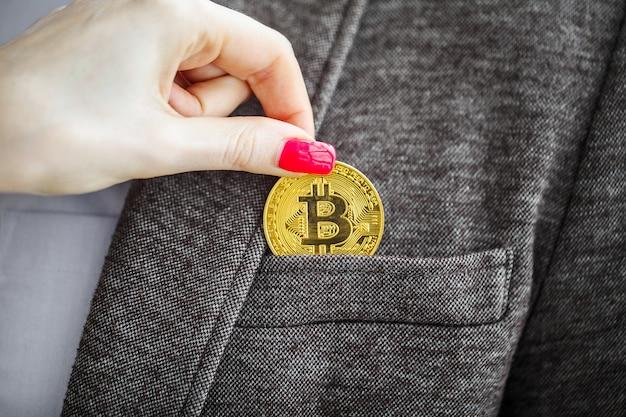 Homme d'affaires enlever ou placer un bitcoin doré dans une poche