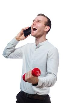 Homme d'affaires, enseignant parlant au téléphone et faisant du sport tient en main un haltère rouge. portrait émotionnel. isolé sur fond blanc