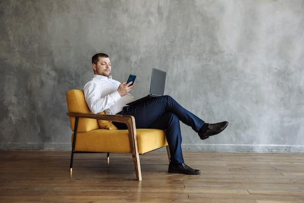 Homme d'affaires envoyant des sms par téléphone et travaillant sur un ordinateur portable dans la chambre