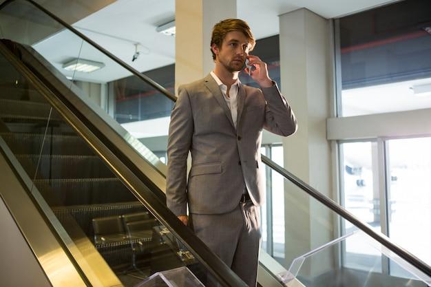 Homme affaires, escalator, conversation, mobile, téléphone