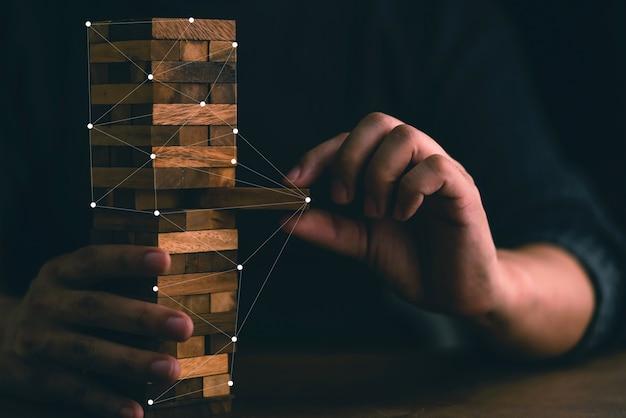 Homme d'affaires essaie de construire un bloc de bois sur une table en bois et un fond noir