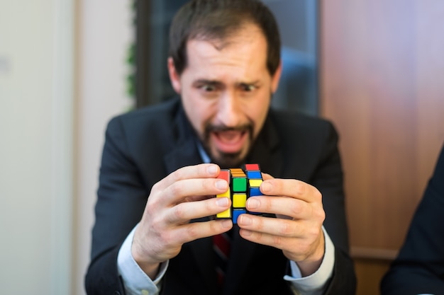 Homme d'affaires essayant de résoudre rubik cube