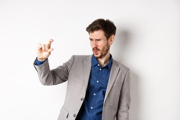 Homme d'affaires essayant de voir quelque chose de petit, montrant la taille de la petite chose avec les doigts