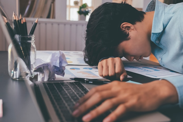 Homme d'affaires a essayé et a souligné le sommeil sur le bureau.